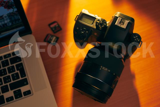 Dslr Camera And SDHC Memory Cards On Desk Near PC