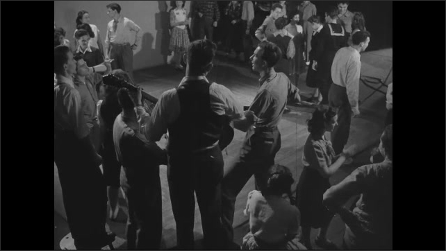 1940s: Pile of cotton in wagon, hands dumb in cotton from basket. High angle, band playing, crowd of people at event, people start to dance.