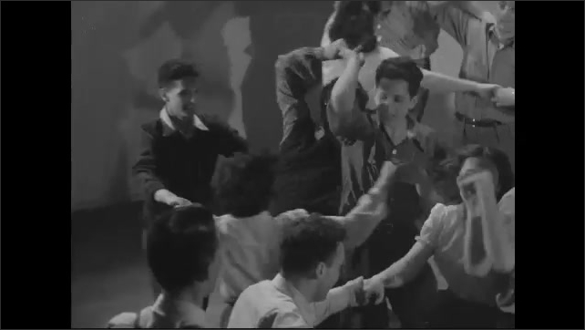 1940s: High angle view of couples square dancing.