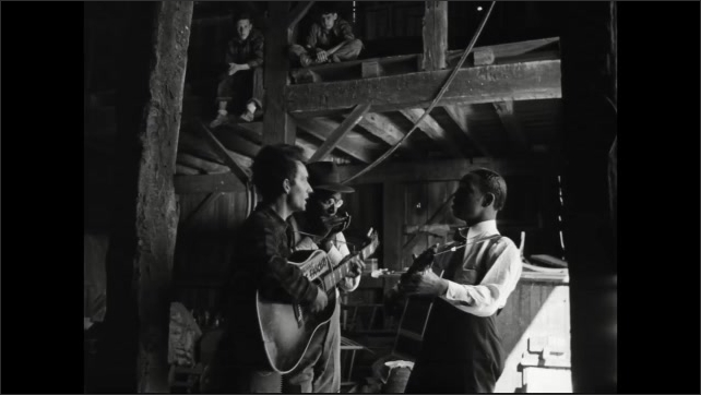 1940s: Men playing instruments, singing in barn, boys watching from loft.
