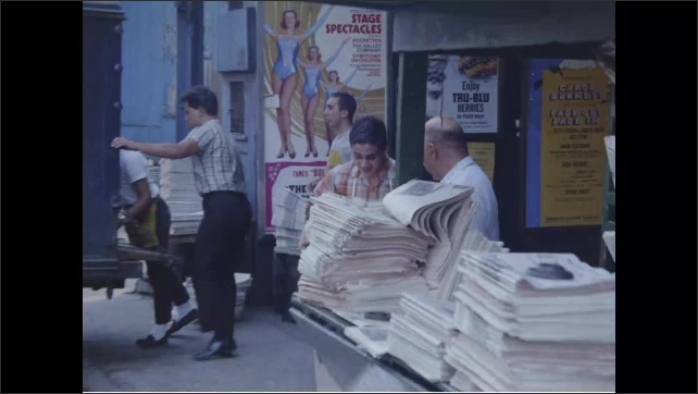 1960s: People walking down sidewalk, heading into city as cars go by on road. Man unloads newspapers from back of truck. Newspapers stacked in front of store. People enter store, buy newspapers.
