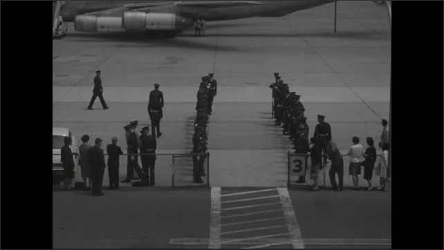 1960s: Soldiers line up in two lines on either side of entrance to building off tarmac on airfield. People board Air Force cargo plane on tarmac.