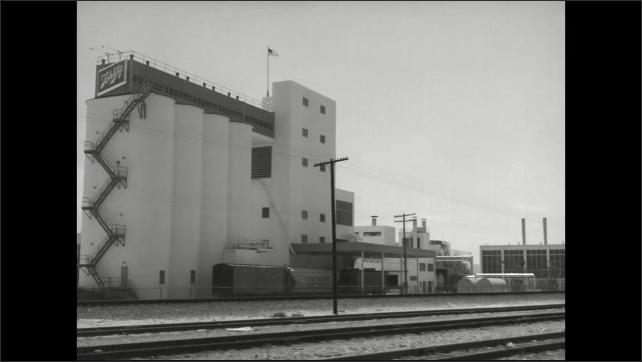 1960s: Cars drive past the Technicolor sign. Grain elevator next to a rail yard.