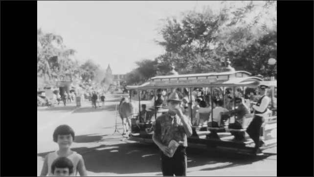 1950s: Horse pulls trolley past crowds in Disneyland. Kids ride log flume at amusement park. Monorail glides on track above crowds and rides at Disneyland.
