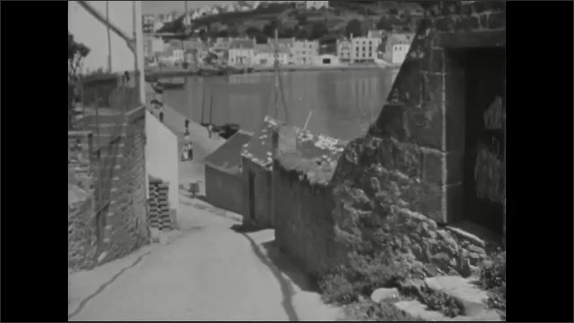 1940s: Old women in village.  Initials carved into rock wall of building.  House.  Women walk towards waterfront.  Boats.  Bridge.  City.