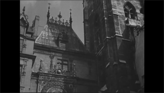 1940s: Herd of sheep graze in field. Lamb carries flag on coat of arms. Ornate clock stands on building in city of Rouen. Child looks out from open window in city house.