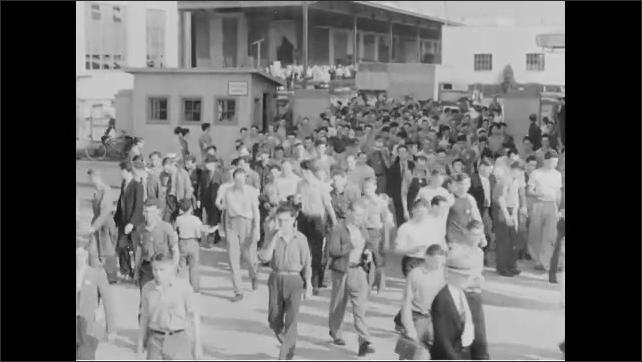 1940s: crowd of people walking through gate