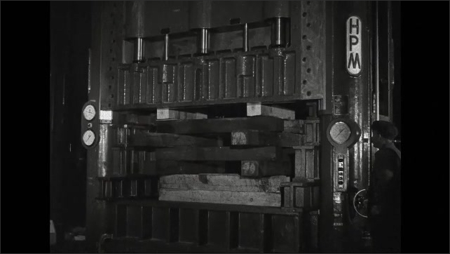 1940s: Large hydraulic press moving up and down slowly, pressing down on stack of square logs. Man watching. Needles on gauges advancing as machine pressing down.