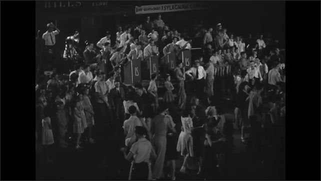1940s: Band plays as crowd of teenage couples dance in auditorium. Children and teenagers watch couples dance near stage.