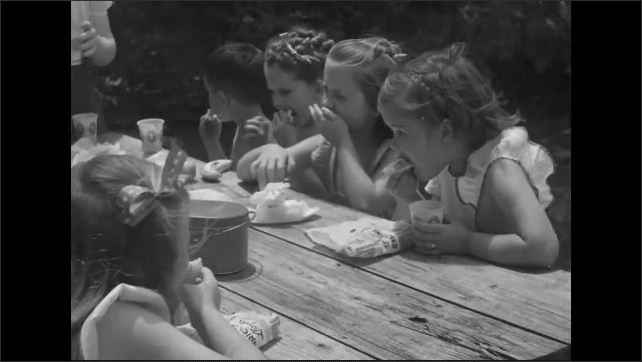1940s: Women and children enjoy refreshments and sandwiches at picnic tables.