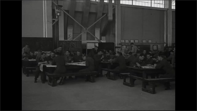 1940s: Air Force cadets consult maps and talk in military hangar.