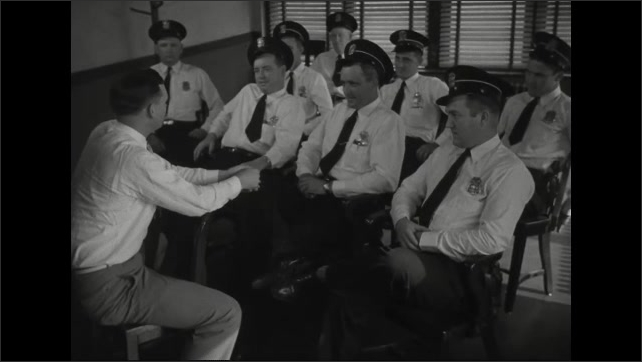 1940s: Man seated in chair in room talks to police officers seated in chairs before him.
