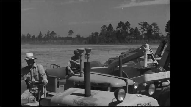 1940s: Tractors in row pull excavating equipment across dirt field.