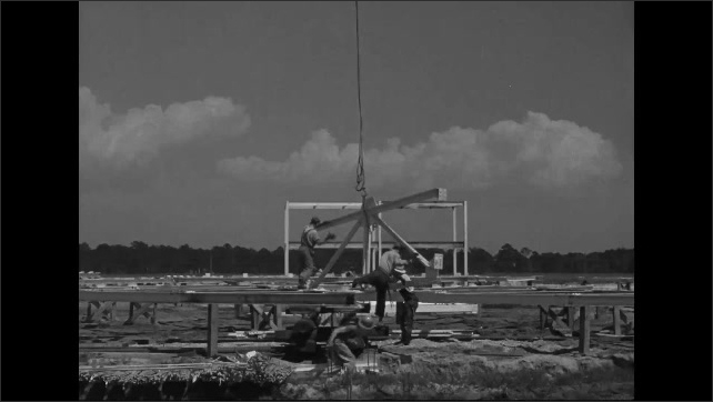 1940s: Workers guide a crane supported steel frame part to the ground.  Workers guide steel frame parts out of a gondola.