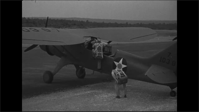 1940s: Pilots stand next to airplanes and put on parachutes. Pilots climb into the cockpit.