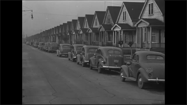 1940s: Cars parked in row on side of street, in front of houses.
