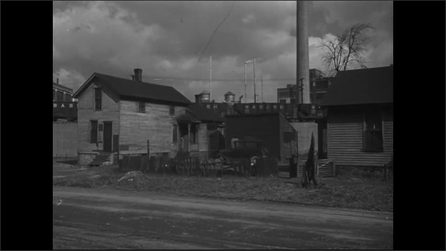 1940s: House with factory behind it. Cars drive by.