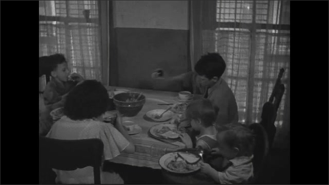 1940s: Kids sit around kitchen table eating meal, baby in high chair.