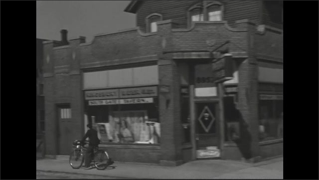 1940s: Street view of city neighborhood Boy on bike with small cart attached cycles past and lady crosses road. Cars and trucks pass on road.