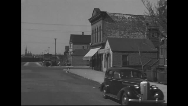 1940s: Street view of city neighborhood and road with close-set houses. Men unload items from car. Girl crosses road.
