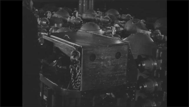1930s: Stacks of assembled rear axles with differential covers. Worker with a forklift places another stack of completed axles. Slate.