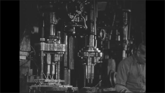 1930s: Drill press makes holes in an automobile part. Workers nearby work on other parts. Slate.