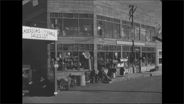 1930s: Car driving past a used item store and lot. Slate.