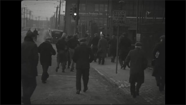 1930s: Men step off bus and walk along crowded sidewalk in city. Men carry lunch bags and enter factory yard.