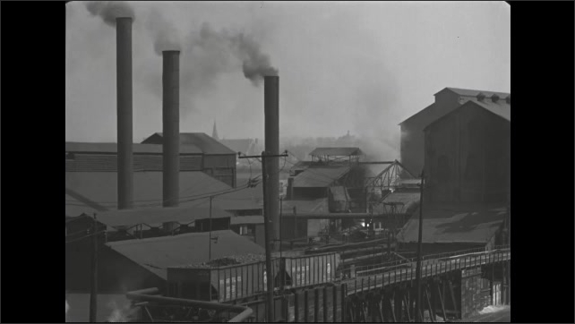 1940s: Smoke pours from tall factory chimneys. A Bessemer converter blows fire among the buildings and then tilts backwards.