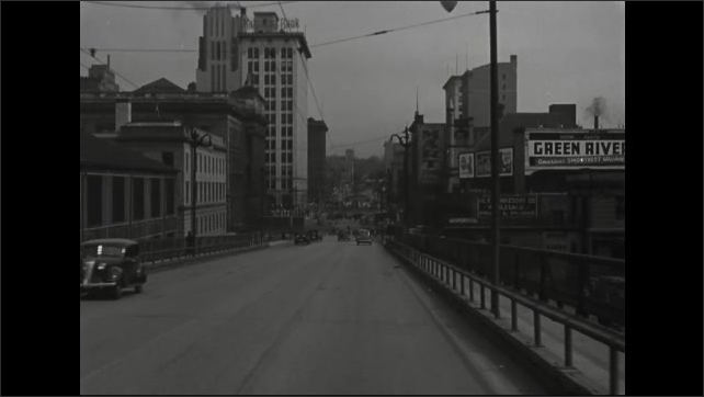 1940s: Driving down road, passed businesses, parked cars, gas station. Driving on road in city over bridge, coming to stop at intersection.