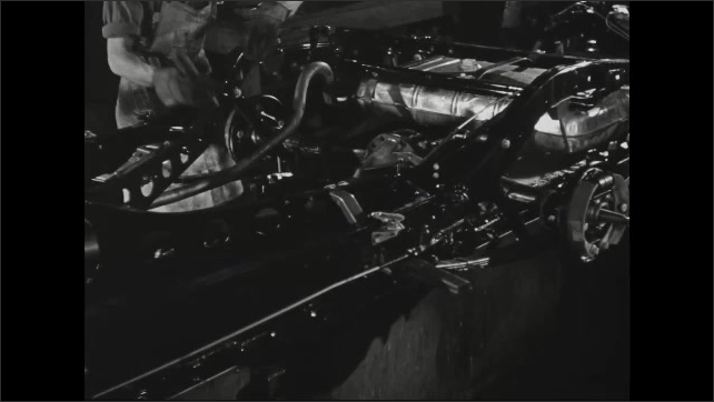 1940s: automobile frame moving down assembly line as worker fasten bolts and screws