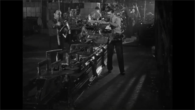 1930s: Slate. Two workers with overhead hoists work an engine assembly line. One worker attaches a clamp to an engine, taps the bottom and places on a conveyor belt.