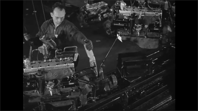 1930s: Workers on an engine assembly line. Two workers clamp engines and move them off the line. Workers return to get another engine.