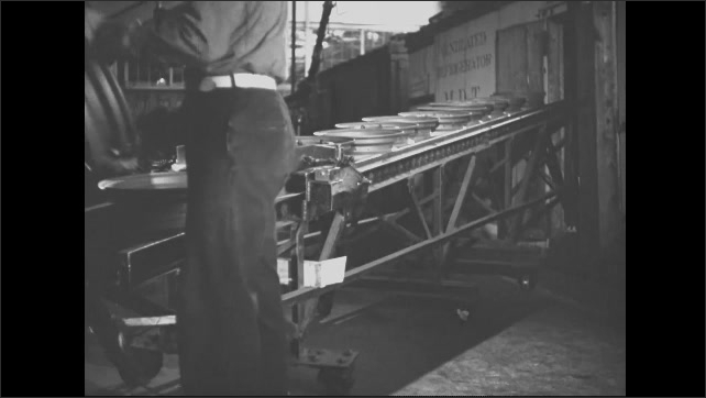 1940s: In factory, tire rims slide down chute as man picks them up and hangs them on hooks on overhead conveyor belt.
