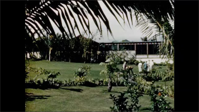 1950s: Woman fastens hibiscus behind tourists ear. Exterior hotel. People ride horses and bikes. Car drives on road in valley.