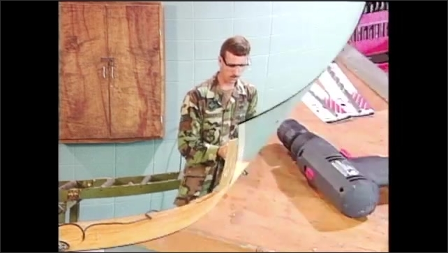 2000s: Man in army fatigues and safety goggles picks up power drill from table, places it over piece of wood and then lowers it. Power drill has level gauge on top. Man holds drill level to wood.
