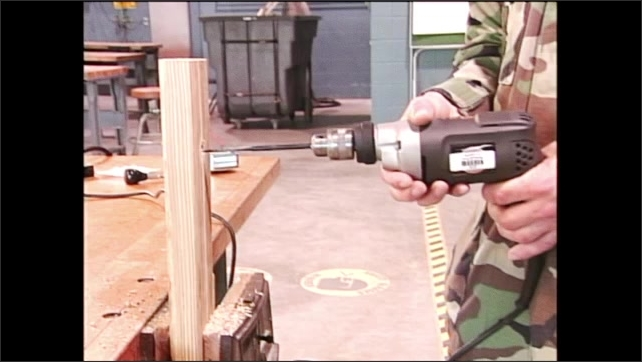 2000s: Man in army fatigues holds power drill with bit in drilled pieced of wood. Man reverses bit direction and pulls it out of wood. Man pulls drill with bit out of hole in wood.