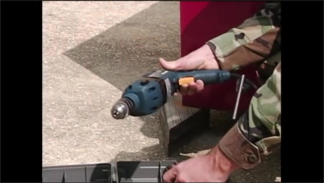 2000s: Man in army fatigues, kneeling on ground, takes power drill out of toolbox and attaches a handle to the front of it.