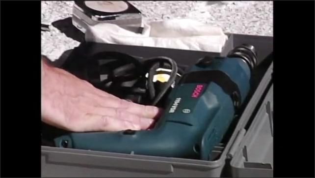 2000s: Person wipes drill bit with cloth then places it in toolbox with power drill and closes the lid.