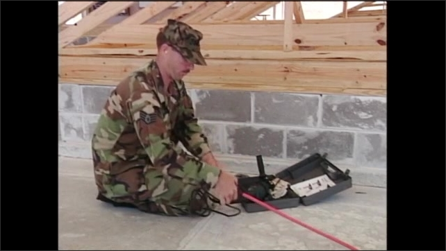 2000s: Man in army fatigues kneeling on ground lays power drill down on open toolbox.
