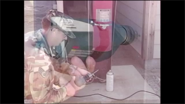 2000s: Man in army fatigues drills hole in side of metal casing with fire extinguisher. Man sprays lubricant onto end of drill bit.