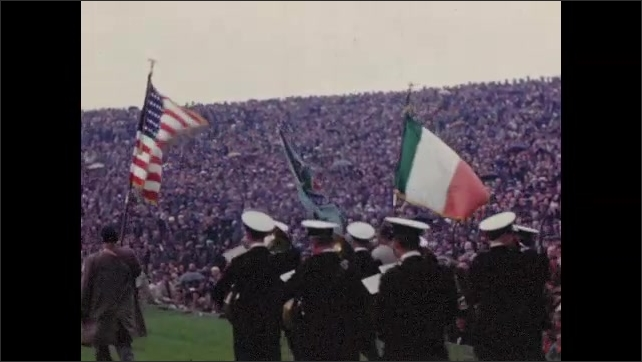 1950s: Men carry flags and lead marching band across hurling field. Men and band march across field before large audience.