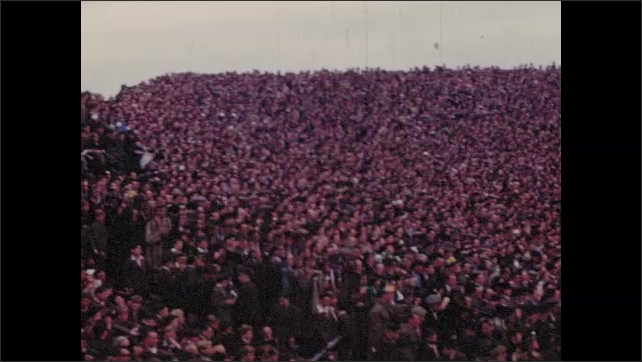 1950s: Large crowd of fans watch sports in hurling stadium. Athletes play hurling before large audience.