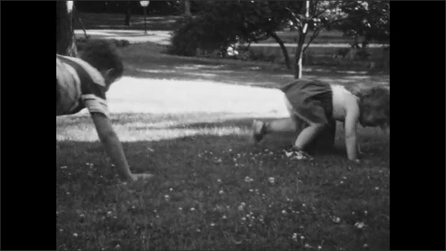 1950s: Boy spins toddler, then falls on the ground.