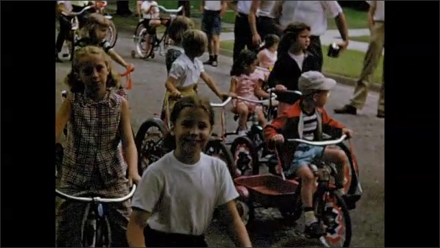 1950s: Adults stand in yard. Man walks toward street and speaks. Kids on bicycles line up on street. Girl waves. Dog jumps on woman.