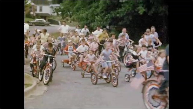1950s: Kids on bikes ride down street behind police car. Adults push children riding tricycles.