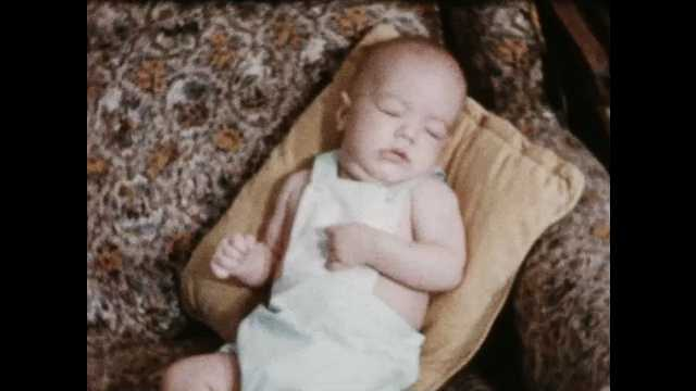 1950s: Sleeping infant rests against pillow on patterned sofa, then is awakened by patting hand.