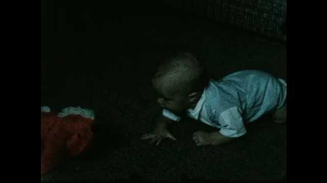 1950s: Baby crawls across carpet toward toy in darkened room.
