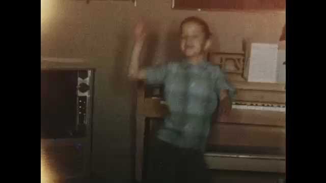 """1950s: Boy performs """"swim"""" dance in front of living room piano; small boy in suspenders dances on living room carpet."""