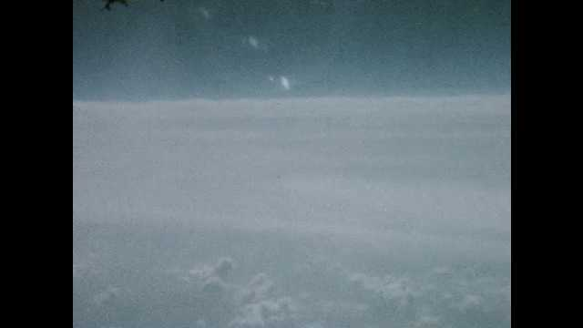 1960s: View of clouds and horizon out of airplane window in flight.
